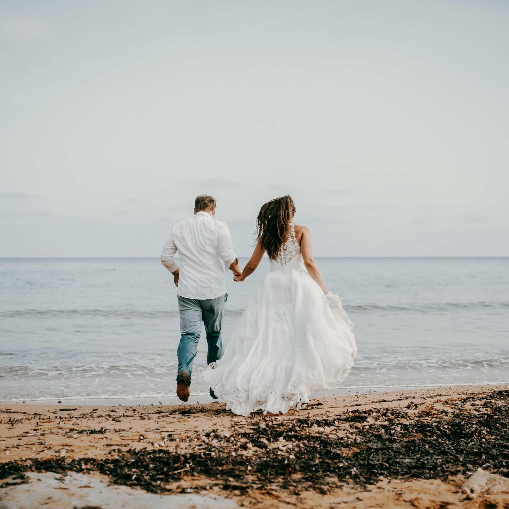 Als Hochzeitsfotograf auf Malta bei einer Strandhochzeit. Das Brautpaar rennt am Strand entlang, berührt mit den Füßen das Wasser, das Haar der Braut weht im Wind. Uns Hochzeitsfotografen Herz schlägt in solchen Momenten schneller.