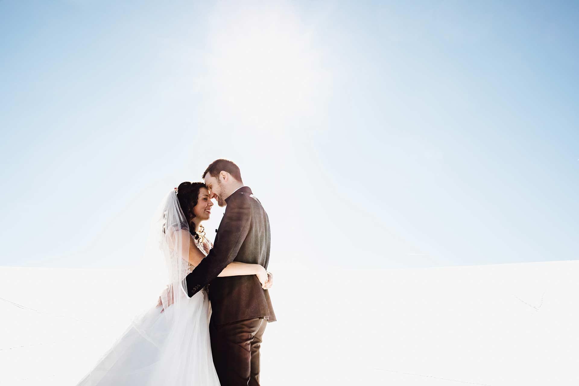 Als Hochzeitsfotograf im Schwarzwald auf dem Öschberghof. Brautpaar steht in einer Winterlandschaft, umgeben von Schnee. Die Sonne scheint und taucht die Umgebung und den Himmel in ein herrliches weiß. Das Brautpaar befindet sich in einer Umarmung und haben ihre Köpfe Stirn an Stirn aneinander gelegt.