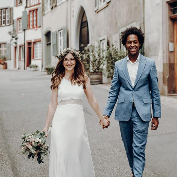 Als Hochzeitsfotograf in Basel! Hier sehen sie das sehr polarisierende Ehepaar Rob und Melanie, welche mit Blick in die Kamera gerichtet freudig die Straße entlaufen. Die Straße ostumgeben von vielen Altbauwohnungen. Die Braut trägt einen Blumenkranz in den Haaren und einen wunderschönen Eukalyptusstrauß in der Hand. Ihr Hochzeitskleid ist in einer A-Linie geschneidert und umspielt ihren Körper mit Leichtigkeit. Rob trägt einen grau blauen Hochzeitsanzug, der seine dunkle Hautfarbe und schwarzen Lockenhaare noch mehr zur Geltung bringt.