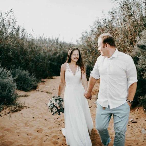 Als Hochzeitsfotograf an der Hochzeit von S&S auf Malta. Das Brautpaar läuft Hand in Hand zwischen den Dünen entlang. Sie trägt ein wunderschönes Hochzeitskleid mit einer A-Linie und einem V- Ausschnitt, der mit Spitze verziert ist. In der Hand trägt die Braut einen Eukalyütusstrauß. Das Brautpaar sieht sich verliebt an. Er trägt sehr lässig schick ein weißes Hemd, die Arme bis zu den Ellbogen gekrempelt in einer Kombination mit einer hellblauen Hochzeitshose, die perfekt zu einer Strandhochzeit passt.