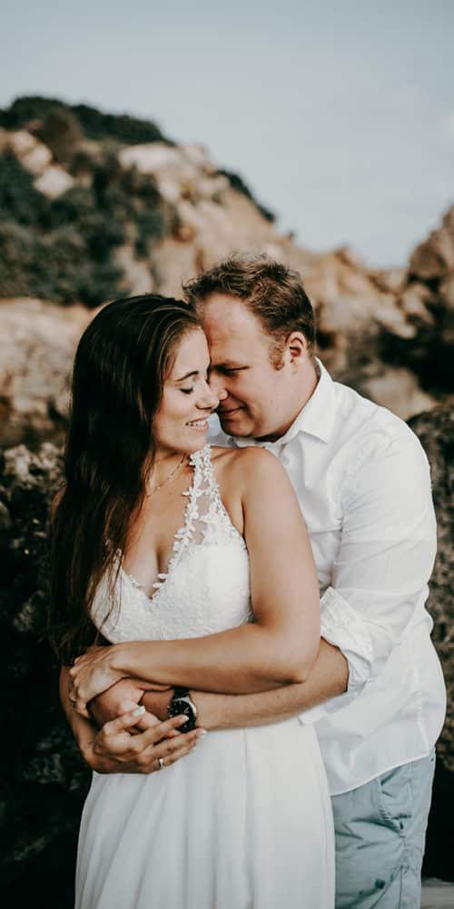 Als Hochzeitsfotograf für S&S auf Malta. Das Brautpaar steht am Strand vor bräunlichen Felsen. Er steht hinter ihr, schließt seine Hände um ihre Taille, sie erwidert seine Umarmung und dreht ihren Kopf zu seinem. Beide haben die Auggen geschlossen und genießen den Moment.