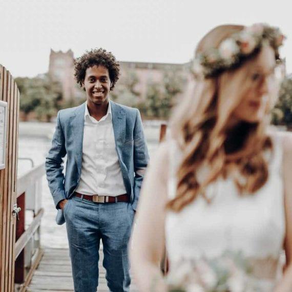 Wir waren als Hochzeitsfotograf an der Hochzeit von Rob und Melanie in Basel geladen. Auf dem Bild sehen sie das Brautpaar versetzt hintereinander steht. Während Rob völlig scharf gestellt ist, sieht man Melanie im Vordergrund eher verschwommen. Der Farbraum des Bildes wird von uns Hochzeitsfotografen bei der Nachbearbeitung auf natürliche Art und Weise an ihren rötlichen Haaren und dem Holzton angepasst.