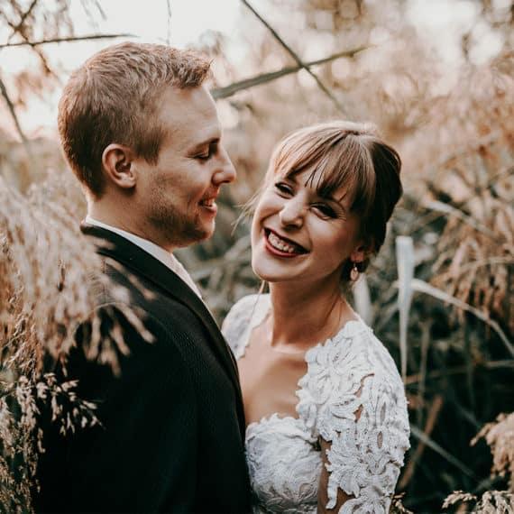 Als Hochzeitsfotograf für Sonja und Jens bei einem After Wedding Hochzeitsshooting am Moosweiher in Freiburg. Das Brautpaar steht inmitten von Schilf. Er sieht sie an, sie blickt zur Seite und lacht. Das Brautkleid der Braut ist aus schöner auffälliger Spitze gefertigt. Solche Bilder mit natürlicher Atmosphäre geschaffen durch Licht und das Momentum lassen unsere Herzen als Hochzeitsfotografen höher schlagen.