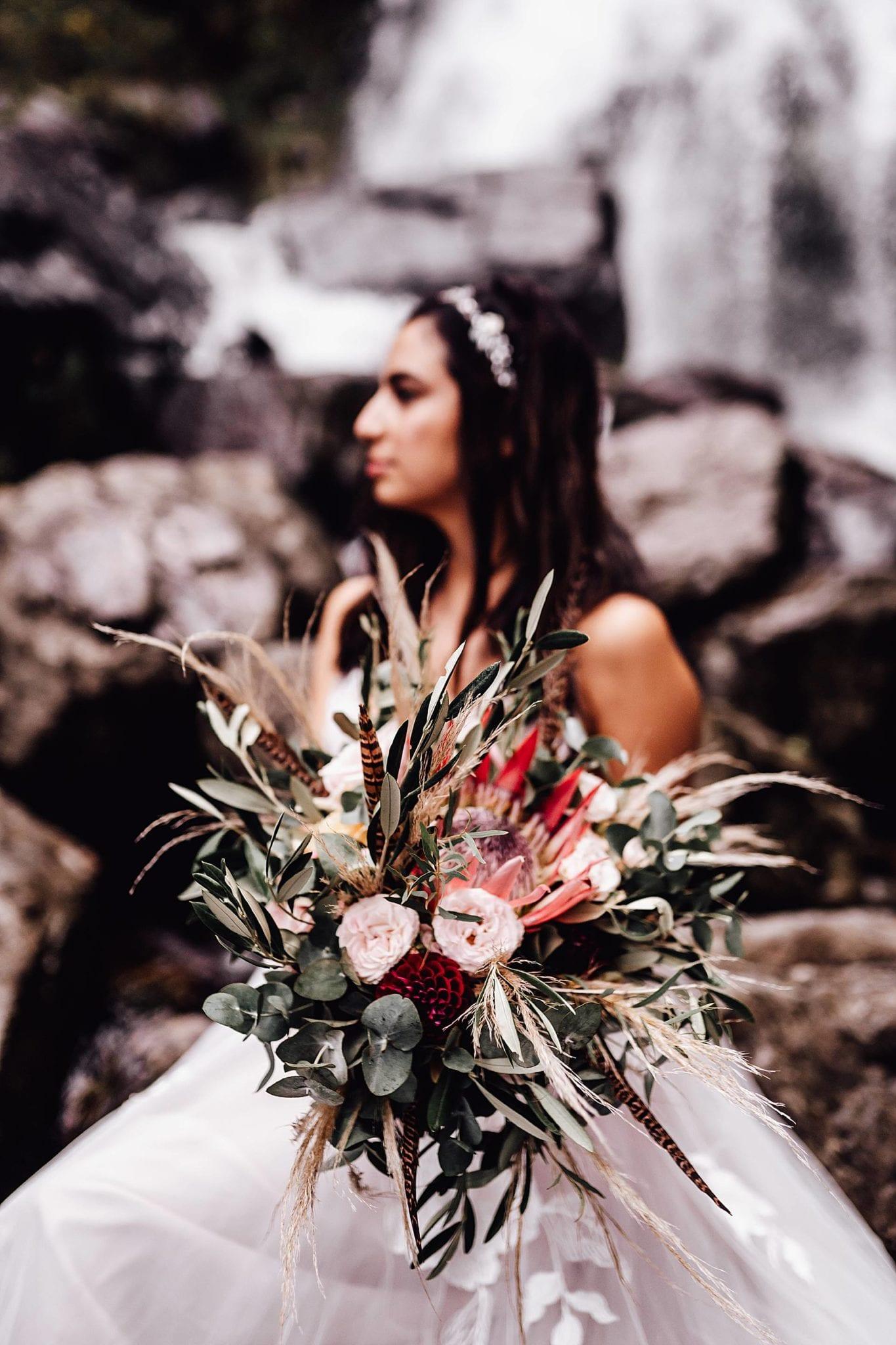 Brautstrauss Pampasgras mit Braut im Hintergrund.
